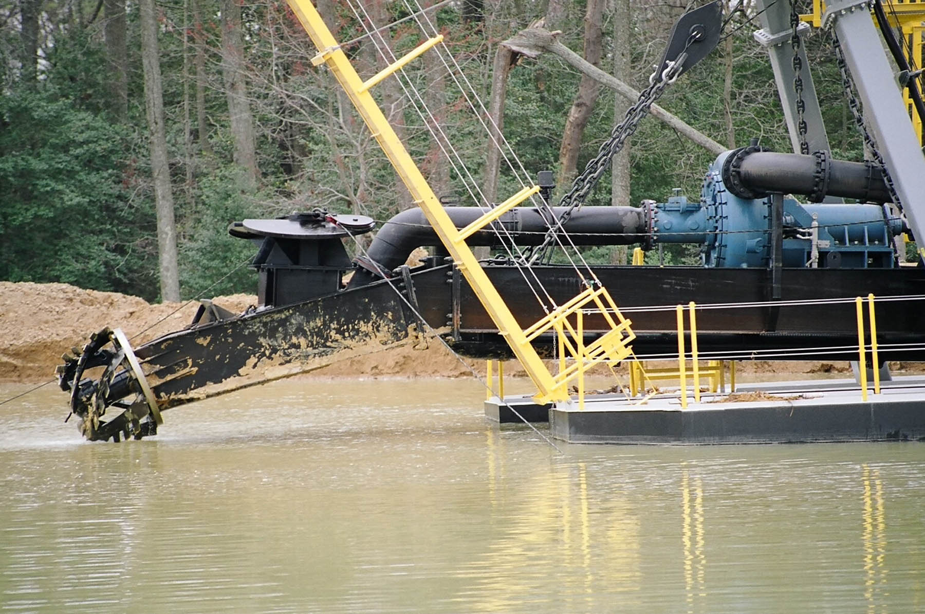 A closer view at a DSC Marlin Class dredge's cutter head being raised out of the river.